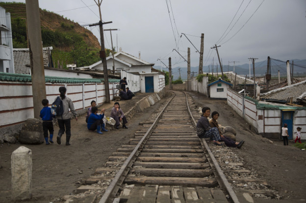 "In this June 20, 2014 photo, North Korean people rest next to the railroad tracks in a town in North Korea's North Hamgyong province. The Associated Press was granted permission to embark on a weeklong road trip across North Korea to the countrys spiritual summit Mount Paektu. The trip was on North Korea's terms. An AP reporter and photographer couldn't interview ordinary people or wander off course, and government ""minders"" accompanied them the entire way. (AP Photo/David Guttenfelder)"