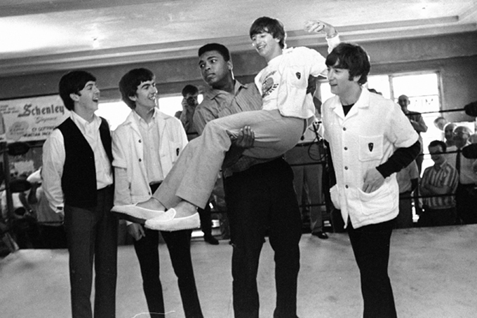 FILE - In this Feb. 18, 1964 file photo, boxer Cassius Clay lifts Beatles member Ringo Starr while the singers visited Clay's camp in Miami Beach, Fla. Others from left are Paul McCartney, George Harrison and John Lennon. A few days earlier the British musicians had appeared for the first time on the Ed Sullivan Show. A week later, Clay would beat Sonny Liston and go on to even greater things as Muhammad Ali. (AP Photo)