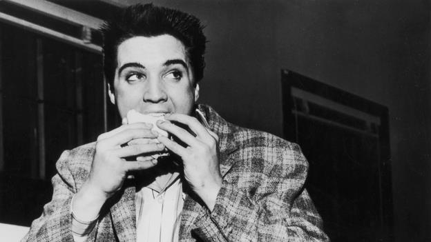 Elvis Presley eating a cheeseburger