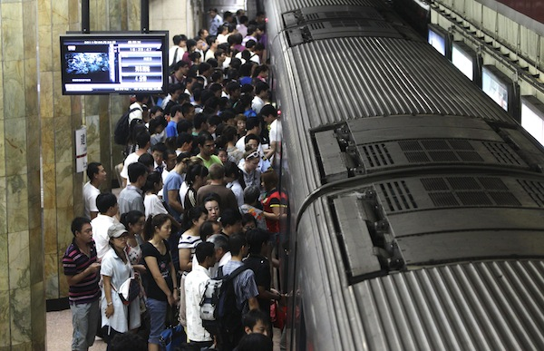 Passengers board a train at a subway station in Beijing